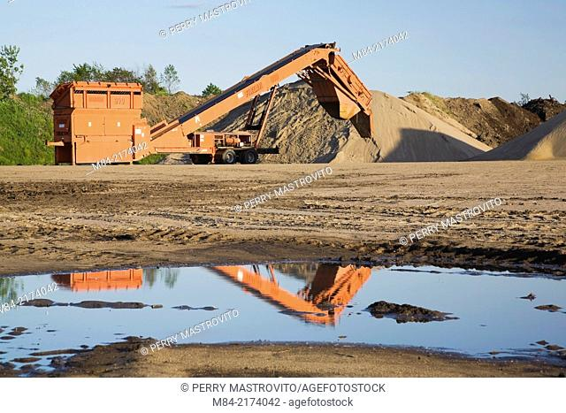 Screener next to some mounds of sand and topsoil in a commercial sandpit after a heavy rainfall, Quebec, Canada