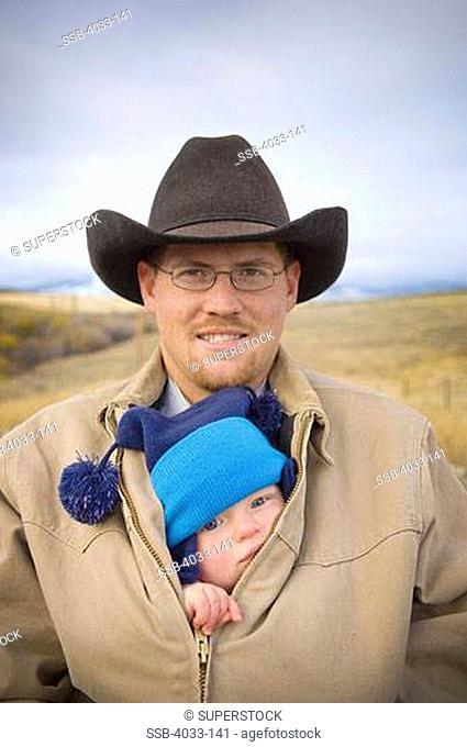 Baby girl peeking from her father's coat, Bozeman, Gallatin County, Montana, USA