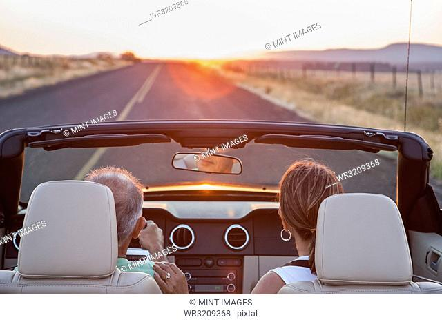 View from behind of senior couple in a convertible sports car driving on a highway at sunset in eastern Washington State, USA