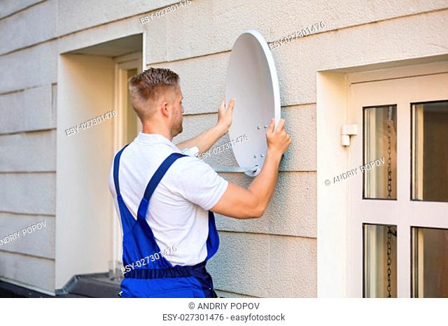 Young Male Technician Installing TV Satellite Dish To Wall
