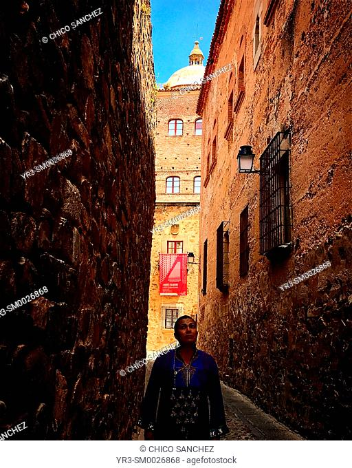 A woman walks in a narrow street of the medieval city of Caceres, Extremadura. The tower of the Toledo-Moctezuma palace is seen in the back