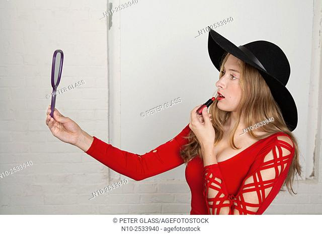 Blonde teenage girl holding a mirror and applying lipstick