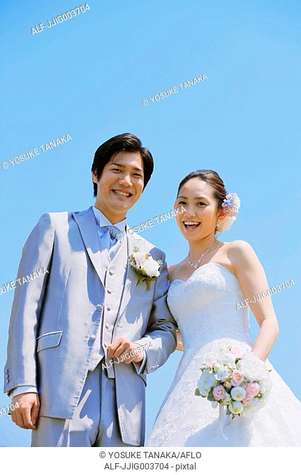 Japanese bride and groom in a city park