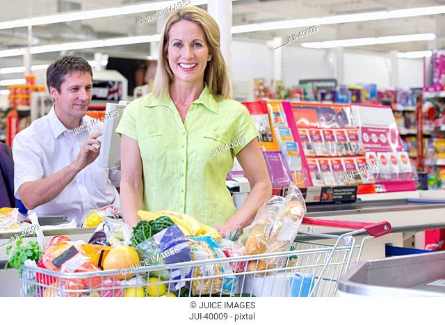 Customer Loading Trolley At Supermarket Checkout