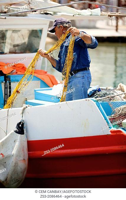 Greek fisherman pulling his net at the port, Mykonos, Cyclades Islands, Greece, Europe