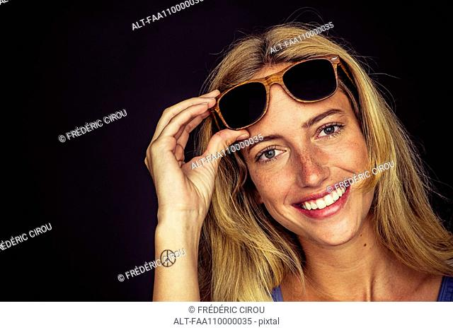 Young woman lifting sunglasses and smiling cheerfully at camera, portrait