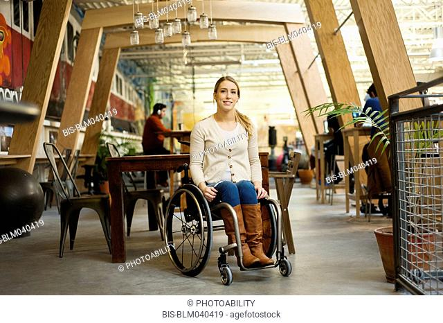 Paraplegic woman sitting in wheelchair in cafe