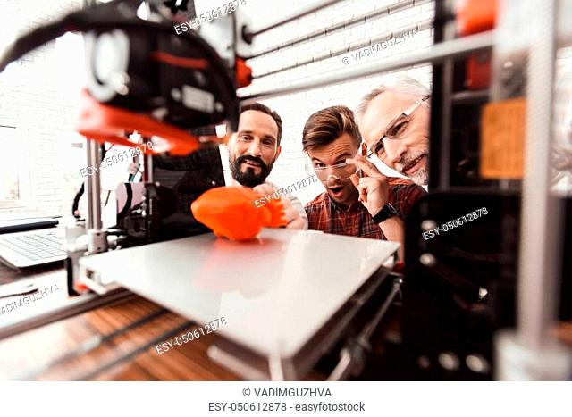 Three men are working to prepare printed model on the 3d model of the heart. They are satisfied with the result. They peer through the working field 3e of the...
