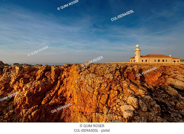 View of Punta Nati lighthouse on sunlit cliff, Menorca, Spain