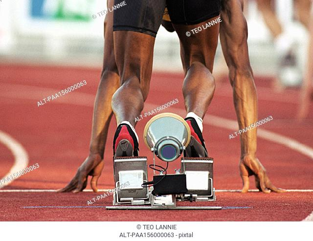 Male runner on starting block, low section, rear view