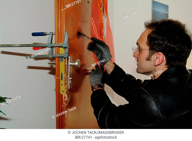 DEU, Germany, NRW: forensic investigator puts coal powder on a broken door, to make fingerprints visible