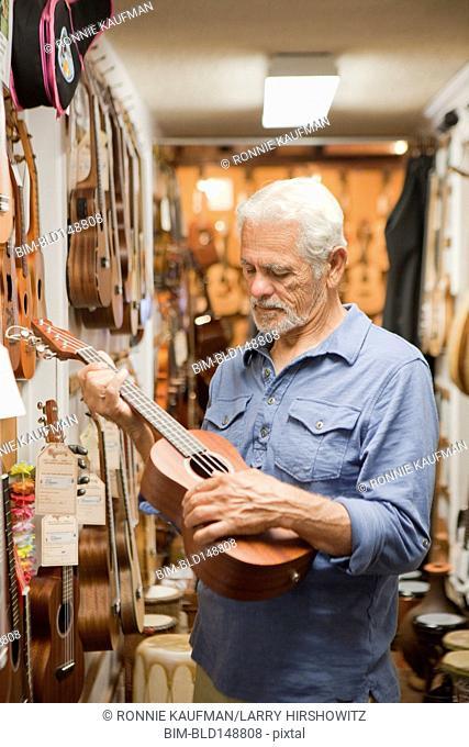 Hispanic craftsman looking at ukulele in shop