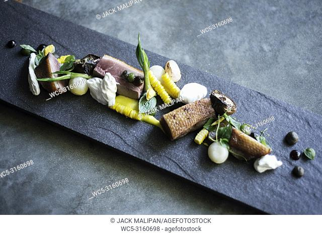 gourmet cuisine grilled pork sour cream and vegetables on modern grey slate