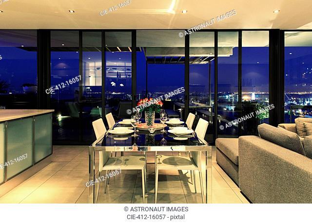 Illuminated modern dining room overlooking city