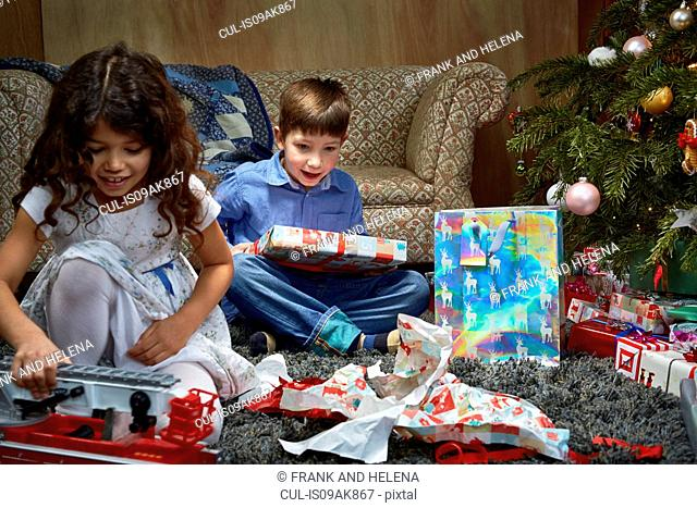 Sister and brother in sitting room unwrapping and playing with christmas gifts