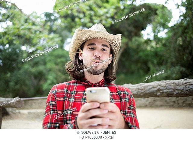 Portrait of man with twig in mouth holding smart phone at park