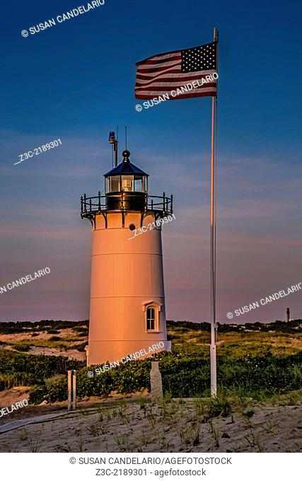 Race Point Lighthouse during sunset next to the American Flag. Race Point is a historic lighthouse and it is located in the northern tip of Cape Cod