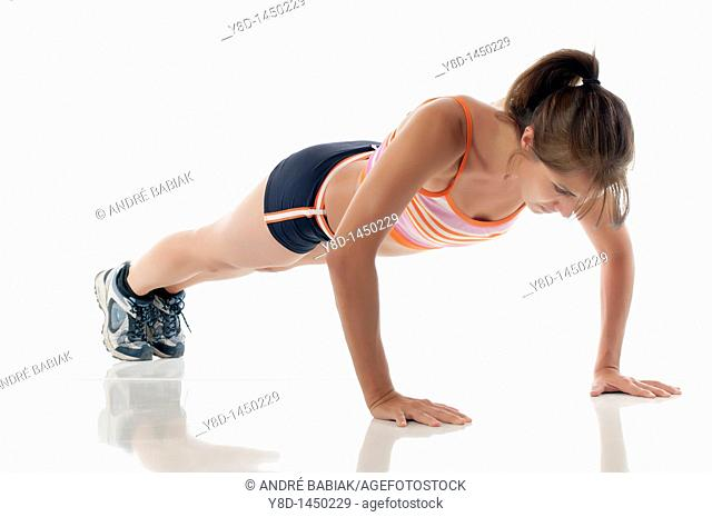 Hispanic fitness woman exercising - Working out by doing push ups