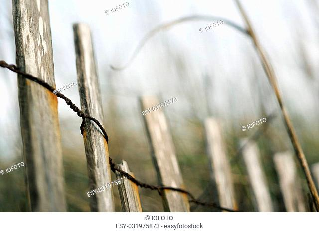 Wooden fence with rusted wiring