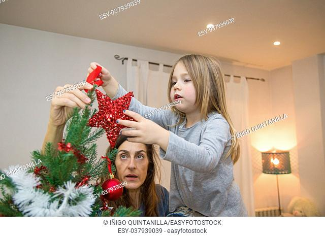 four years blonde cute girl and mother at home decorating Christmas tree and placing a red star in the top