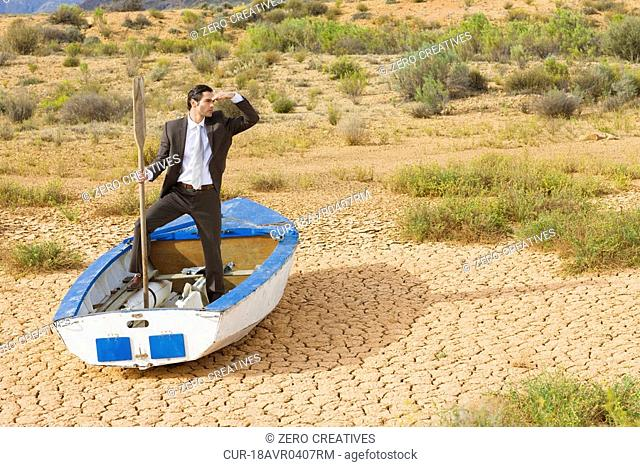 Businessman, rowing boat, dry desert