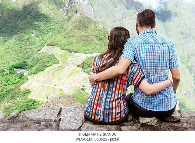 Peru, couple sitting and enjoying the views of Machu Picchu citadel