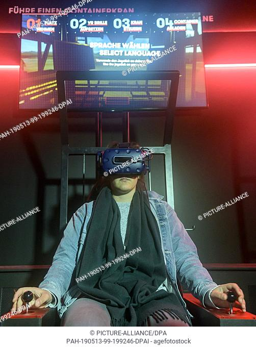13 May 2019, Hamburg: A visitor of the Discovery Docks virtually controls a container gantry crane with the help of VR glasses during the opening of the harbour...