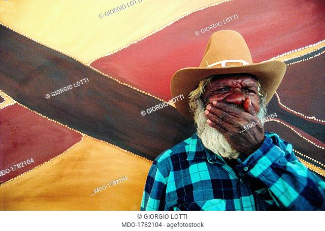 Half-length portrait of the Australian Rover Thomas wearing a straw hat, while covering his mouth with a hand, on the background of a multicoloured panel; first...