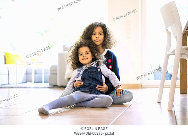 Little girl sitting on floor in living room, holding her sister, portrait