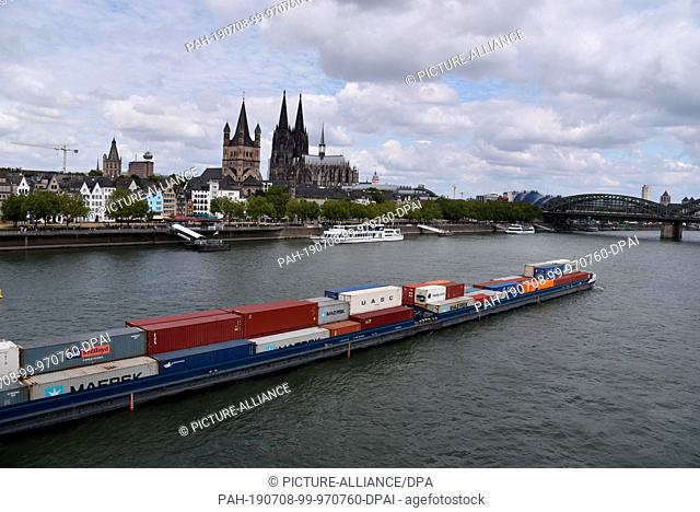 07 July 2019, North Rhine-Westphalia, Cologne: Cologne city view, The Rhine with jetty and the churches Gross St. Martin and the Cologne Cathedral Photo: Horst...