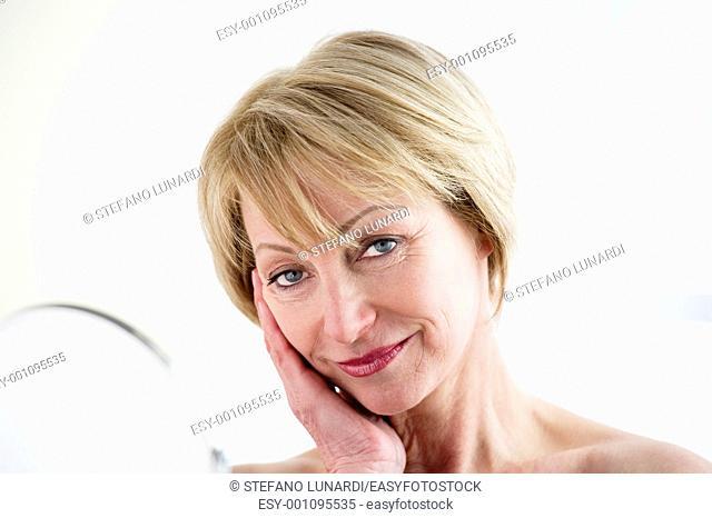 Beautiful mature woman making up