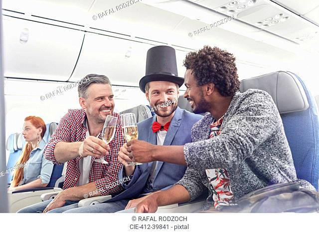 Young male friends toasting champagne glasses in first class on airplane