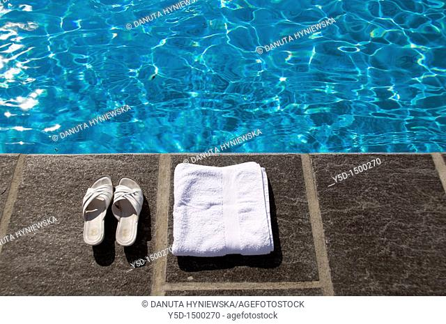 swimming pool in summer, no people, shoes and towel at poolside,  Geneva, Switzerland