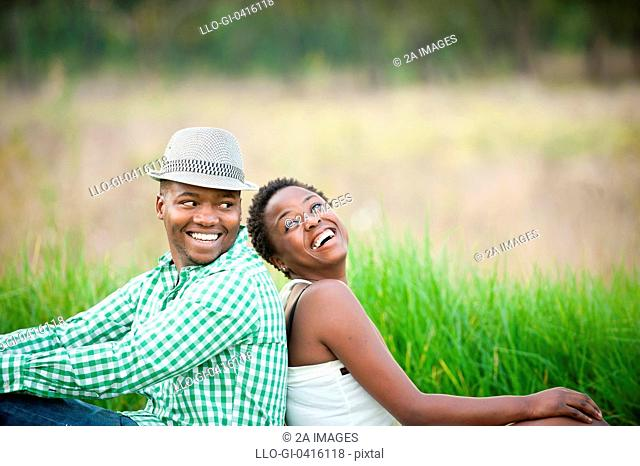 Young couple laughing while sitting back to back in park, Johannesburg, South Africa