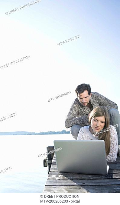 Young couple wooden jetty working laptop