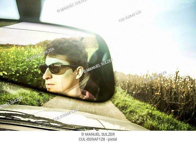 Mirror reflection of young man leaning driving on country road