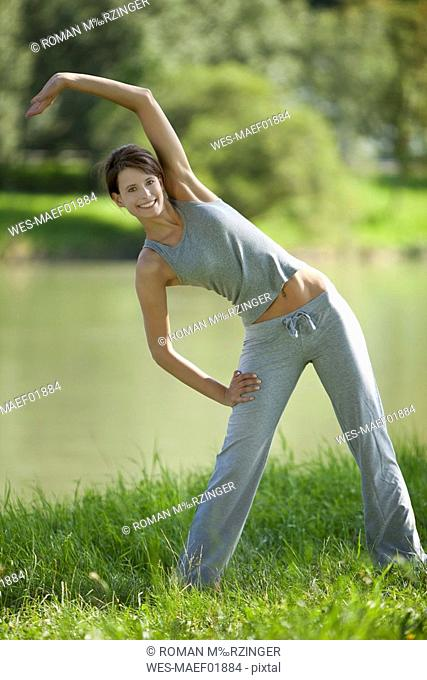 Germany, Bavaria, Woman stretching in the meadow