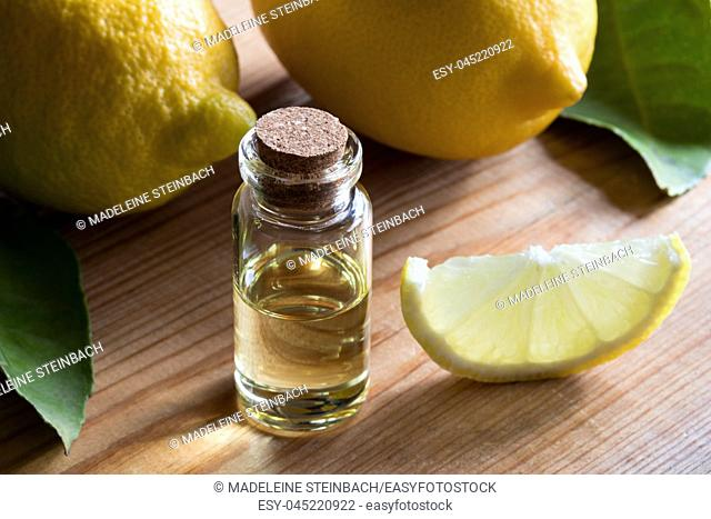A bottle of lemon essential oil on a wooden table, with lemons in the background