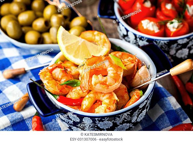 Selection of spanish tapas appetizers - shrimps, pepper, olives, corn and glasses of beer