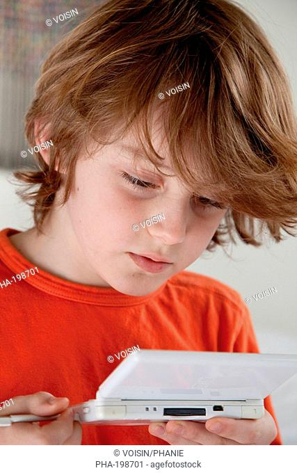 9 years old boy playing with video game console
