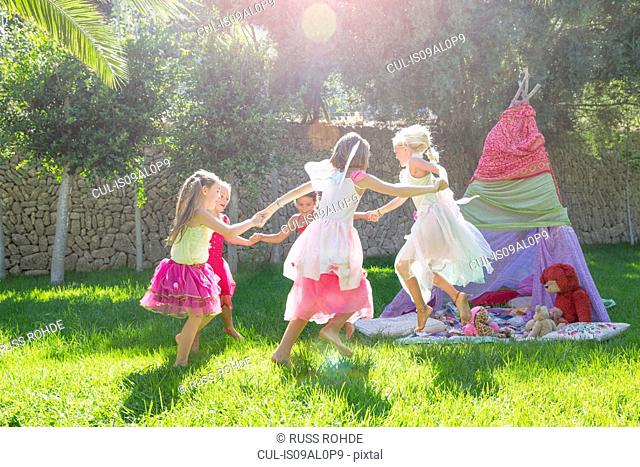 Five girls in fairy costume playing in garden