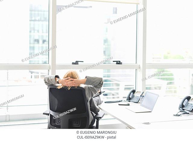 Rear view of businesswoman sitting on office desk chair looking out of window