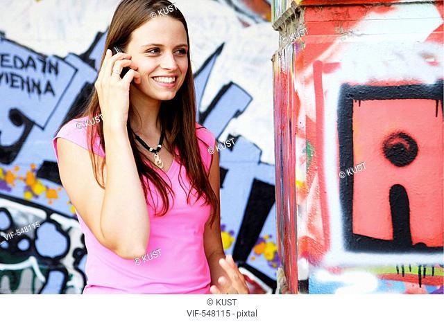 junge Frau telefoniert vor Graffitiwand. - Austria, 25/07/2007
