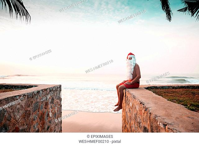 Thailand, man dressed up as Santa Claus sitting on wall in front of the sea at sunset