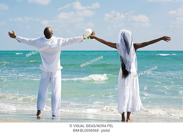 African bride and groom with arms outstretched