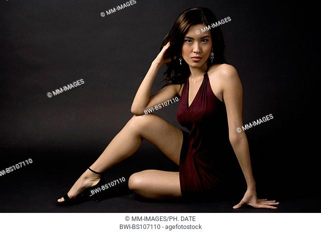 attractive Asian woman in a short evening dress sitting on floor