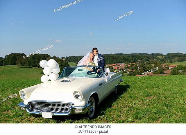 Portrait Of Bride And Groom In Open Top Car On Wedding Day