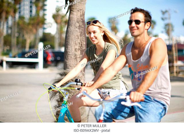 Happy couple cycling together at Venice Beach, Los Angeles, California, USA
