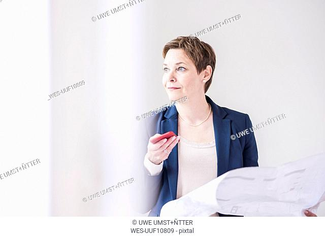 Confident real estate agent holding plan and cell phone
