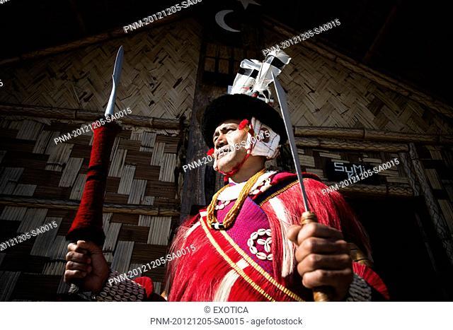 Naga tribal warrior standing with spear outside a hut, Hornbill Festival, Kohima, Nagaland, India